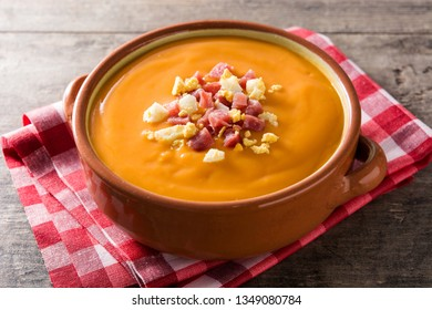 Typical Spanish salmorejo cream with ham and egg on wooden table.