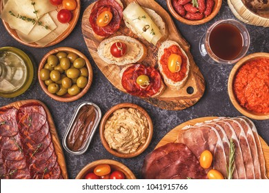 Typical spanish tapas concept. Concept include slices jamon, chorizo, sausage, bowls with olives, tomatoes, anchovies,  mashed chickpeas, cheese.
