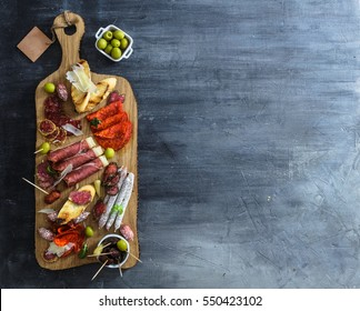 Typical spanish tapas concept. include variety slices jamon, chorizo, salami, bowls with olives, peppers, anchovies, spicy potatoes, mashed chickpeas on a wooden table. Copyspace