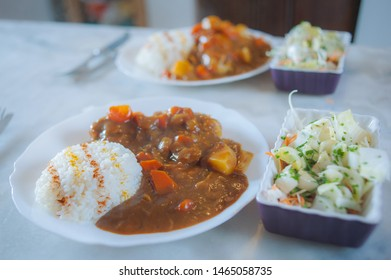 Typical spicy Japanese curry rice with carrot and potatoes, served with rice and fresh salad