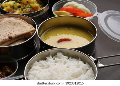Typical Stainless steel Lunch Box or Tiffin with Maharashtrian food menu Chapati OR Roti, Plain Dal Tadka, White Rice Potato sabji with salad and pickle