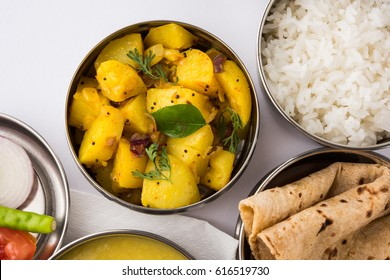 Typical Stainless steel Lunch Box or Tiffin with North Indian or Maharashtrian food menu Chapati OR Roti, Plain Dal Tadka, White Rice and Potato OR Cauliflower sabji with salad, selective focus