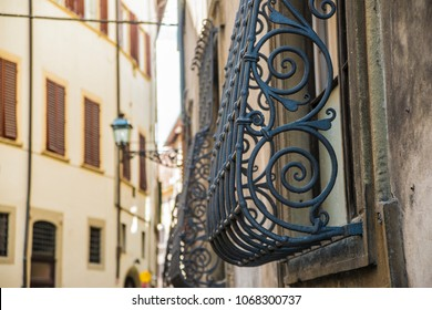 Typical stone houses with wrought iron window grills in narrow street. Florence, Italy, Europe.Big window with wrought-iron grating in shabby house, Street details in old centre of Florence.