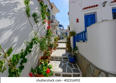 Typical stone slated alley with limewashed houses and bougainvilleas in Kythnos, Greece