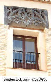 Typical street of Toledo, Spain, Balcony with metal latticework in a window of an old building of Toledo, a world heritage city,