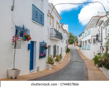 Typical street with white houses and plant pots in Benalmadena Pueblo