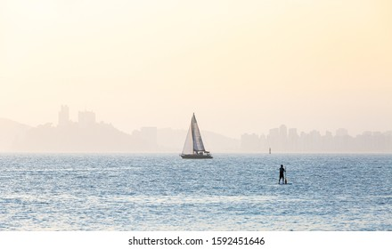 Typical summer afternoon scene in the city of Santos, with sailboats and stand up paddle practitioner.