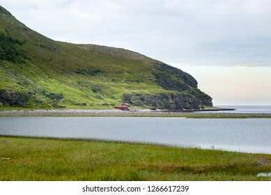 A typical summer landscape for the northernmost part of Norway near the Nordkapp tunnel. Calm sea bay with red wooden fishing houses under a green hill, Finnmark, Norway.