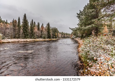 Typical Swedish river landscape in winter at Mörkret with river flowing from Lake Syndre-Fulusjön and shores with conifers and deciduous trees covered with snow against gray sky