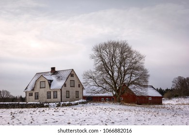 Typical swedish wooden farmhouse and barn in the rural landscape in winter.