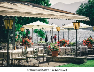 Typical terrace restaurant table at romantic luxury Ascona town on Lake Maggiore, Ticino canton, Switzerland. Expensive family breakfast and dining in street cafe and bar in Swiss in summer. Veranda