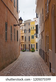 a typical town street in ciutadella menorca with winding curved cobbled road old traditional painted houses and street lamps
