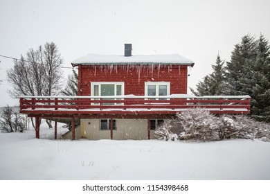 Typical traditional arctic red house with snow and icicles located in the mountains on a fjord.
