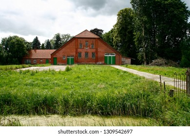 typical traditional farmhouse made of bricks in the district Wesermarsch (Germany) behind a fresh green meadow with misty sky