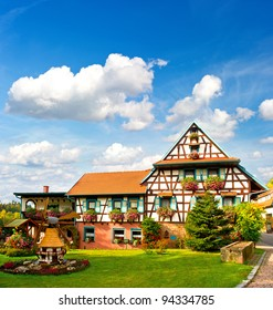 typical traditional house in the Black Forest, Southern Germany. european landscape with flowers garden and cloudy blue sky
