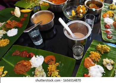 Typical traditional items of a Kerala meal (sadya) on a dining table. Various curries and pickles are arranged on tender banana leaves. Top view.