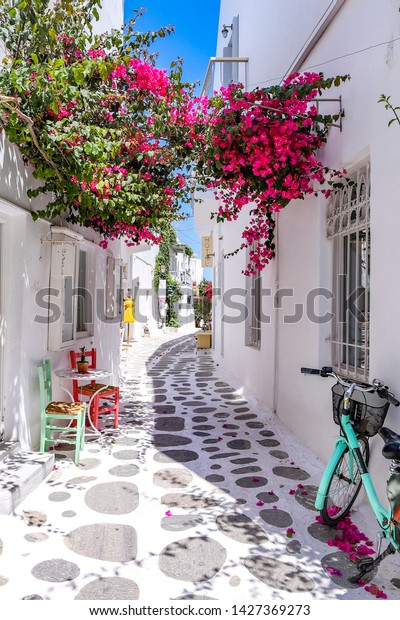 The typical traditional whitewashed alleys of Cyclades islands with colorful flowers at Parikia or Paroikia town during summer time. Paros Island, Aegean Sea,  Greece - June 8, 2019