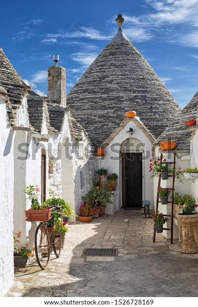 Typical trulli decorated with plants and flowers in Alberobello, Italy