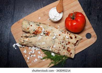 Typical Turkish meal Gozleme with herb and cheese on light wooden cutting board on black table.