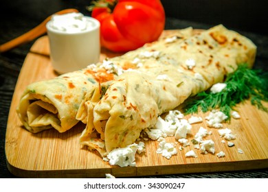 Typical Turkish meal Gozleme with herb and cheese on light wooden cutting board on black table. Toned.