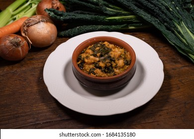 """typical Tuscan """"Ribollita"""" bread and vegetable soup in terracotta bowl from the wooden table of an old tavern"""