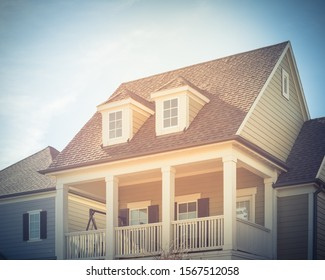 Typical two story country-style residential house in suburbs Dallas. White painted porch patio with banister, dormer roof and weathered shingle siding tiles