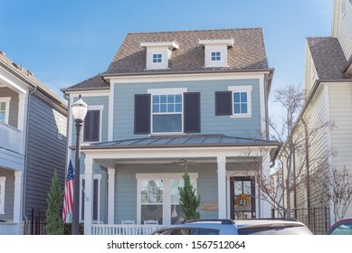 Typical two story country-style residential house with American flag in suburbs Dallas. White painted porch patio with banister, dormer roof, weathered shingle siding