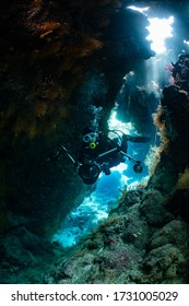 typical underwater cave in a red sea reef with an underwater photographer diver