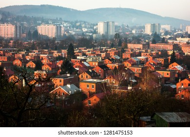 Typical and unique functionalist urban area with small red brick family houses and gardens in foreground and hillwith forest on background in town Zlin, Czech republic.
