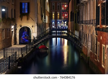 Typical Venetian canal with bridge and Illuminated Christmas tree, night view, Venice, Italy