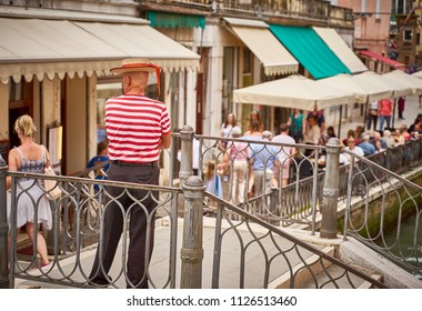 Typical Venetian gondolier in traditional clothing is waiting for customers