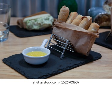Tequeños typical Venezuelan food, cheese fingers served in paper bag on stone plate