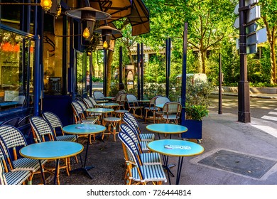 Typical view of the Parisian street with tables of brasserie (cafe) in Paris, France.  Architecture and landmark of Paris. Cozy Paris cityscape