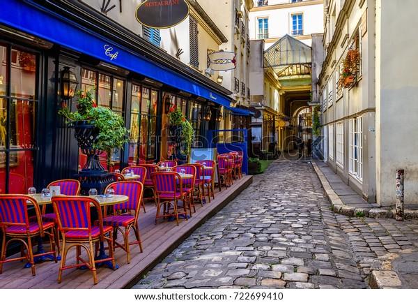 Typischer Blick auf die Pariser Straße mit Tischen mit Tischen des Cafés in Paris, Frankreich. Architektur und Wahrzeichen von Paris. Gemütliches Pariser Stadtbild