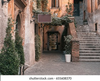 Typical vintage Italian street with ivy plant hanging off the walls and staircase