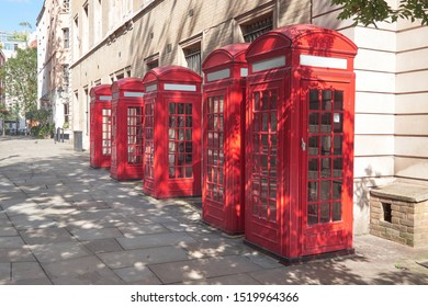 Typical vintage red telephone booths on sunny street in London, England