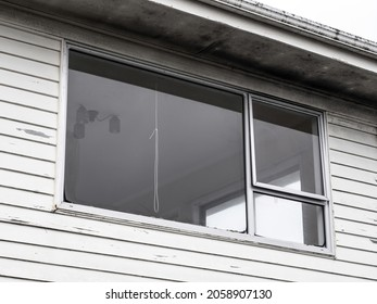 Typical window with aluminum frame on weatherboard wall. New Zealand suburban architecture.