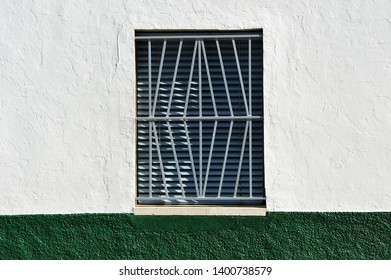 Typical window of andalusian village with gray iron fence and louvered shutter, Spain