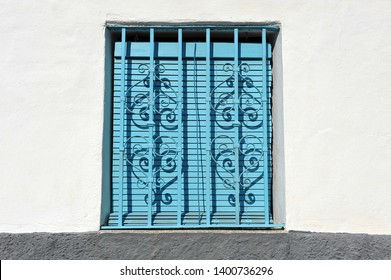 Typical window of andalusian village with iron fence and blue shutter, Spain