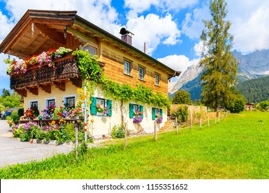 Typical wooden alpine house decorated with flowers on green meadow in Going am Wilden Kaiser mountain village on sunny summer day, Tyrol, Austria