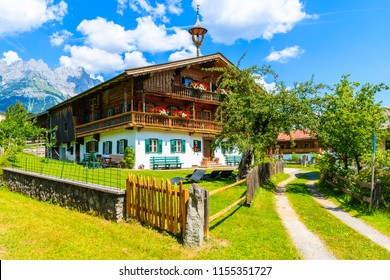 Typical wooden alpine house decorated with flowers on green meadow in Going am Wilden Kaiser village on sunny summer day, Tyrol, Austria