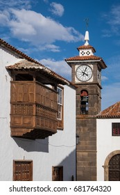 Typical wooden balcony and view of the clock tower of the church of the village of San Juan de la Rambla in the north of Tenerife, Canary Islands