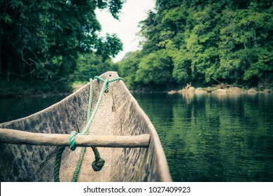 typical wooden canoe chopped from a single tree by indigenous people navigating along a river in the Ecuadorian Amazonian jungle