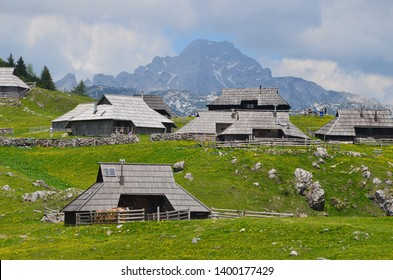 Typical wooden cottages on the mountain of Velika planina, Slovenia, the Kamnik Alps in the background