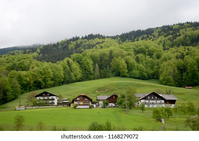 Typical wooden houses in the Austrian alps. They are three stories high with sloping roofs. Behind them are green hills covered with forest. The sky is grey.