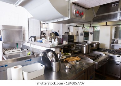 Typical working kitchen interior in restaurant with variety of equipment, utensils and foodstuffs