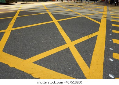 Typical yellow street markings and lines of a pedestrian crossing in downtown Hong Kong, China