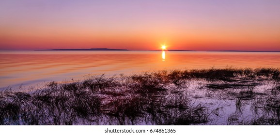 A typically beautiful summer sunrise over the Straits of Mackinac at the Old Mackinac Point Lighthouse, Mackinac City Michigan, USA