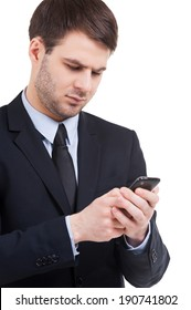 Typing a business message. Confident young man in formalwear holding mobile phone and looking at it while standing isolated on white