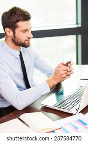 Typing business message. Top view of young man in shirt and tie holding mobile phone and looking at it while sitting at his working place